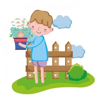 La pianta da appartamento di sollevamento del ragazzo con recinta il paesaggio