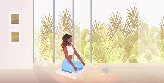 La posa di loto di seduta della donna afroamericana la bella ragazza che fa l'yoga esercita il concetto sano di stile di vita