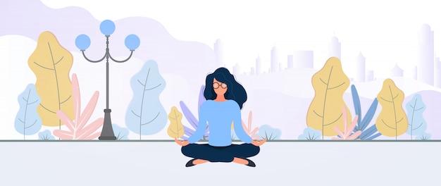 La ragazza medita nel parco. la donna è impegnata nello yoga. concetto di stile di vita sano.