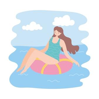 La ragazza prende il sole sull'anello nella piscina, concetto di viaggio di vacanze estive