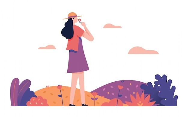 La ragazza sente l'odore della freschezza dei fiori nel giardino