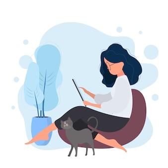 La ragazza si siede su un pouf e lavora al tablet. una donna con un tablet è seduta su un grande pouf. il gatto si strofina contro la gamba della ragazza.