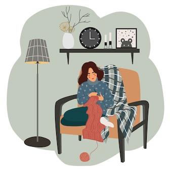 La ragazza si siede su una sedia accanto alla lampada da terra e lavora a maglia sullo sfondo della mensola interna con un orologio, un vaso, un'immagine e candele