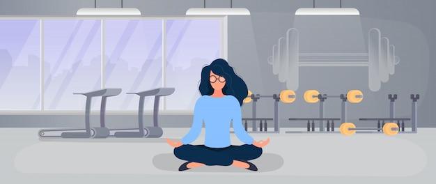 La ragazza sta meditando in palestra. la ragazza fa yoga in palestra. il concetto di sport e stile di vita attivo.