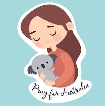 La ragazza sveglia che abbraccia l'orso di koala e prega per l'australia