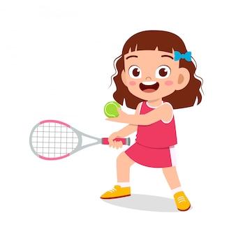 La ragazza sveglia felice del bambino gioca a tennis del treno