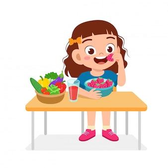 La ragazza sveglia felice del bambino mangia l'alimento sano