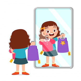La ragazza sveglia felice del bambino sceglie i vestiti