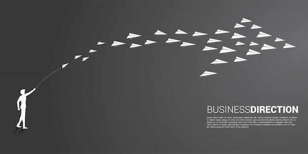 La siluetta dell'uomo d'affari che getta l'aeroplano di carta bianco di origami è sistemata in una forma di grande freccia