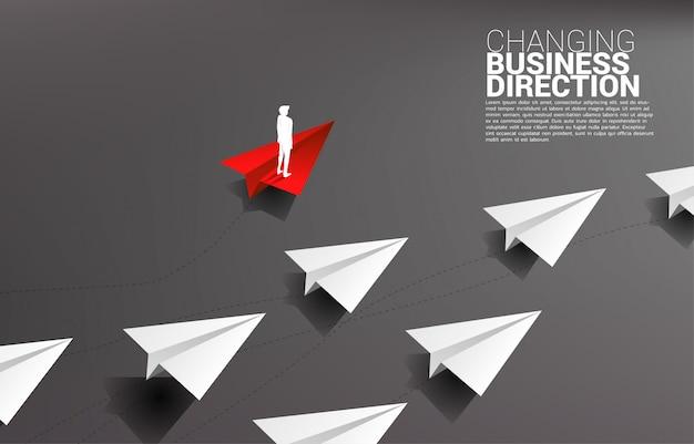 La siluetta dell'uomo d'affari che sta sull'aeroplano di carta rosso di origami è allontanamento della direzione dal gruppo di bianco. concetto di business di interruzione e marketing di nicchia