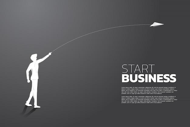 La siluetta dell'uomo d'affari getta l'aeroplano di carta di origami. concetto di affari di avviare attività e imprenditore