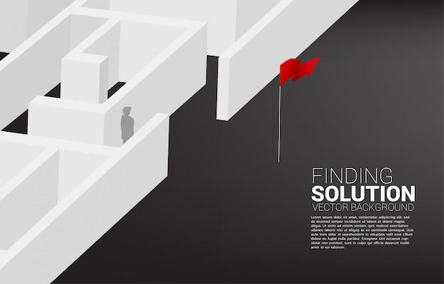La siluetta dell'uomo d'affari trova l'uscita da labirinto alla bandiera rossa. concetto di business per trovare soluzione e raggiungere l'obiettivo