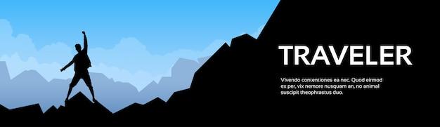 La siluetta dell'uomo del viaggiatore sta sulla roccia della montagna
