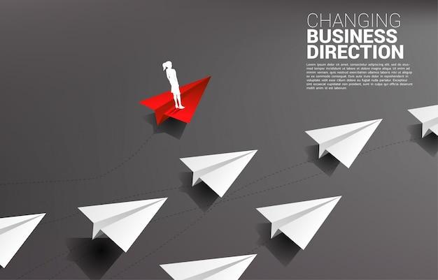 La siluetta della donna di affari che sta sull'aeroplano di carta rosso di origami è allontanamento della direzione dal gruppo di bianco. concetto di business di interruzione e marketing di nicchia
