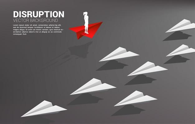 La siluetta della donna di affari che sta sull'aeroplano di carta rosso di origami va in modo diverso dal gruppo di bianco. concetto di business di missione di interruzione e visione.
