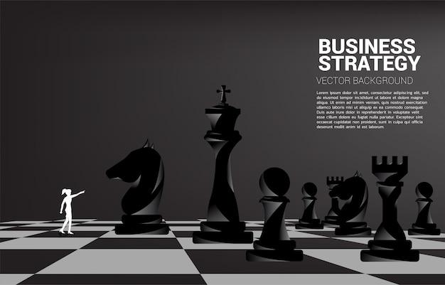 La siluetta della donna di affari indica in avanti con il pezzo degli scacchi. concetto di marketing strategia aziendale.