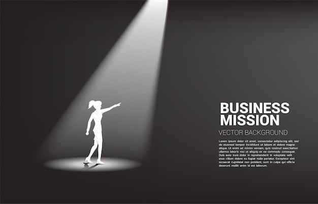 La siluetta della donna di affari indica in avanti sotto i riflettori