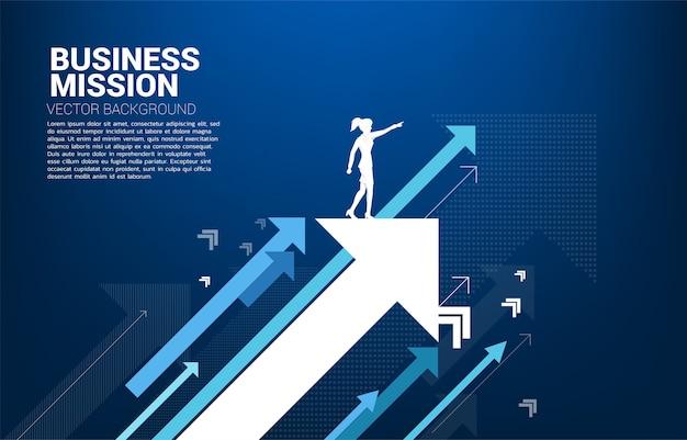 La siluetta della donna di affari indica in avanti sull'aumento della freccia. concetto di crescita aziendale e leadership.