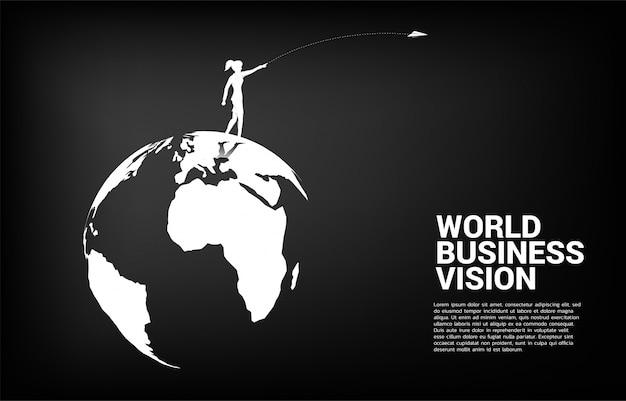 La siluetta della donna di affari lancia l'aeroplano di origami sul globo del mondo. il concetto di missione di visione del mercato business mondiale si avvia