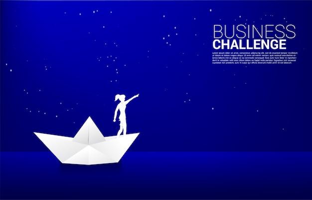 La siluetta della donna di affari negli origami della nave di carta indica di star nel cielo alla notte. concetto di rotta verso il successo. goal mission vision successo nel percorso di carriera.
