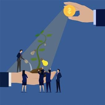 La squadra di affari che pianta l'albero di idea irriga la terra per crescita.