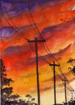 La vista del bellissimo cielo serale con pali elettrici e la silhouette degli alberi.