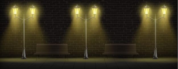 Lampioni che si accendono sul fondo del muro di mattoni