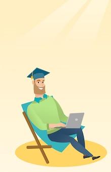 Laureato seduto in chaise longue con computer portatile.