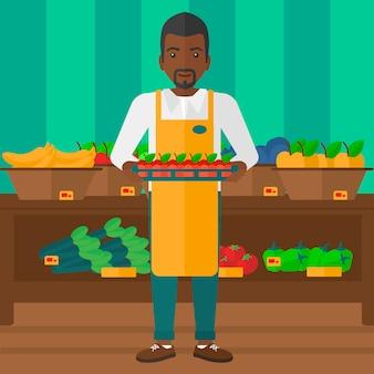 Lavoratore del supermercato con scatola piena di mele