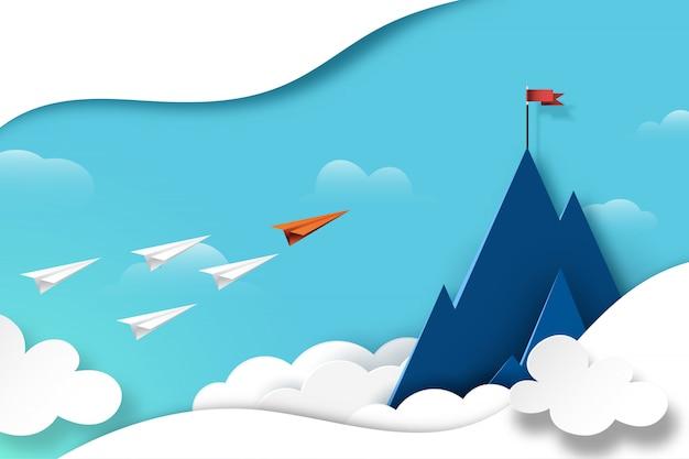 Lavoro di squadra dell'aeroplano di carta che vola alla bandiera rossa sulla cima della montagna.