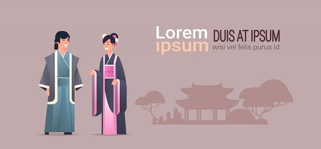 Le coppie asiatiche che indossano i vestiti tradizionali equipaggiano la donna in costume antico che sta insieme i caratteri cinesi o giapponesi sopra lo spazio orizzontale integrale della copia del fondo delle costruzioni della pagoda