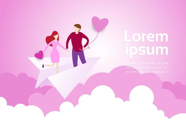 Le coppie che si tengono per mano volano sull'aereo di carta sopra il rosa
