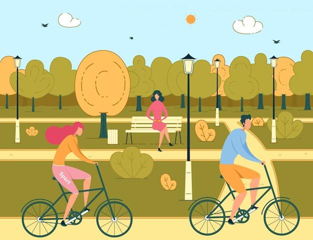 Le coppie della donna e dell'uomo guidano le biciclette in parco pubblico