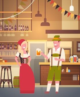 Le coppie in pub che indossano i vestiti tradizionali bevono la birra nel concetto del fest dell'uomo e della donna di celebrazione del partito di oktoberfest della barra
