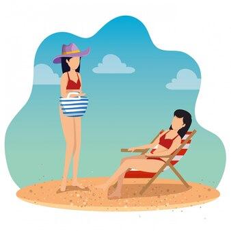 Le donne che indossano il costume da bagno con cappello e concia sedia