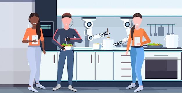 Le donne che utilizzano app mobile controllo uomo umanoide con fili elettrodi indicatori a portata di mano robot chef utile preparare cibo robot assistente concetto moderno cucina interno orizzontale