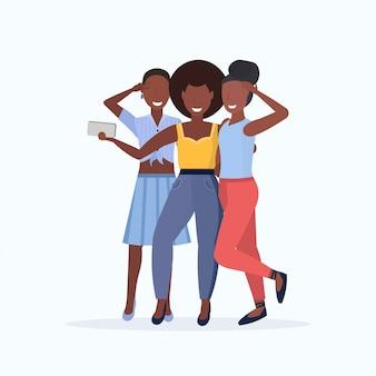 Le donne raggruppano la presa della foto del selfie sui personaggi dei cartoni animati femminili della macchina fotografica dello smartphone che stanno insieme la posa sul fondo bianco integrale