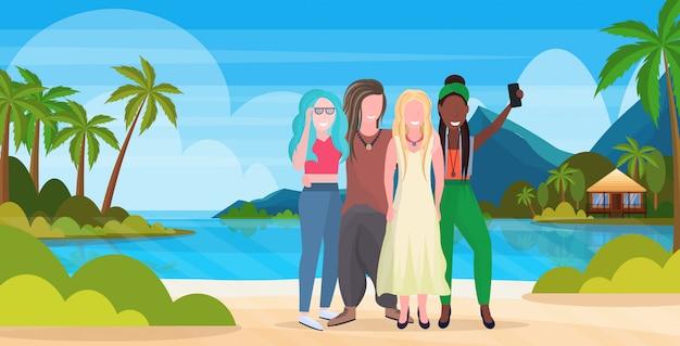 Le donne raggruppano sulla spiaggia che prende la foto del selfie sugli amici della corsa della miscela di concetto di vacanze estive della macchina fotografica dello smartphone che stanno insieme orizzontale integrale del fondo tropicale della spiaggia dell'isola