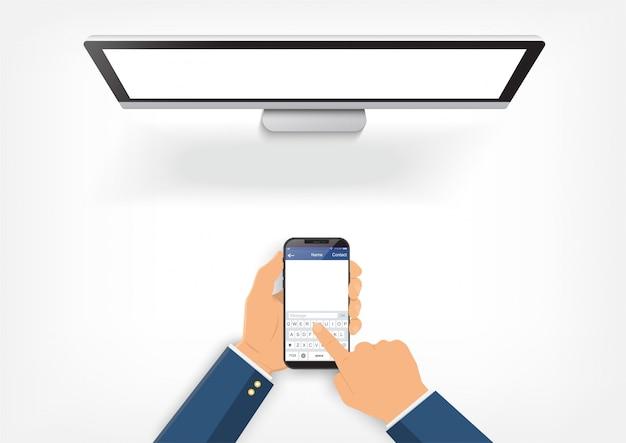 Le mani che tengono smartphone è collegato al computer.