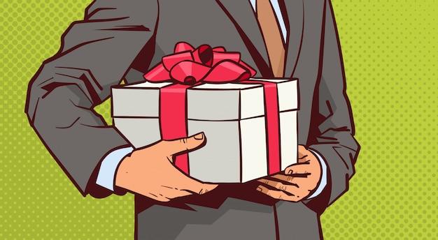 Le mani del regalo della tenuta dell'uomo di affari, schizzano la scatola attuale con l'arco rosso del nastro sul fumetto