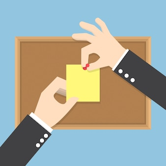 Le mani dell'uomo d'affari appuntano le note appiccicose sull'albo del sughero