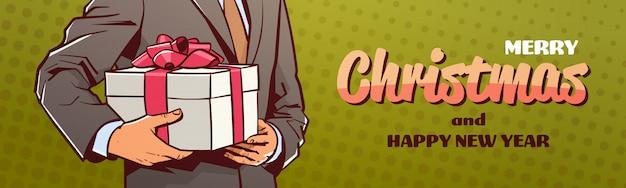 Le mani dell'uomo d'affari che tengono il presente del contenitore di regalo di buon natale insegna il buon anno