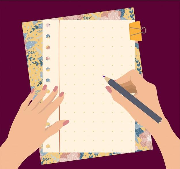 Le mani femminili tengono una matita con il blocchetto per appunti bello dei fiori