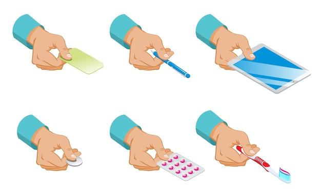 Le mani maschii isometriche tengono l'insieme delle pillole della moneta della compressa della penna della carta e dello spazzolino da denti isolati