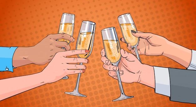 Le mani raggruppano il bicchiere tintinnante del vino di champagne che tosta fondo di pin up di pop art retro