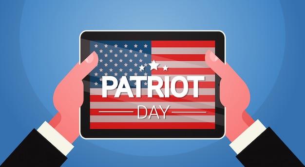 Le mani tengono il computer della compressa con l'insegna nazionale di festa di giorno di patriota di usa della bandiera degli stati uniti