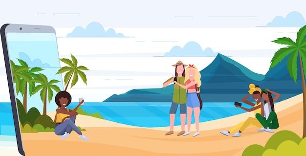 Le persone che usano i cellulari mescolano uomini donne che si rilassano sull'orizzontale integrale di app mobile dello schermo dello smartphone di concetto di dipendenza digitale di vacanze estive della spiaggia tropicale dell'isola
