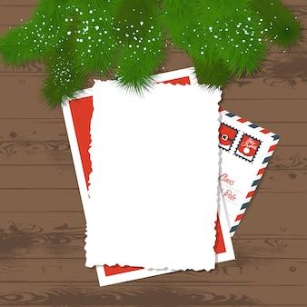Lettera di natale con rami di abete sul tavolo di legno