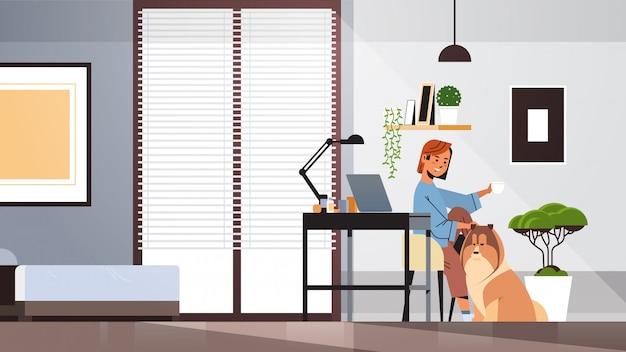 Libero professionista della donna che per mezzo del computer portatile che lavora a casa durante l'autoisolamento della quarantena del coronavirus