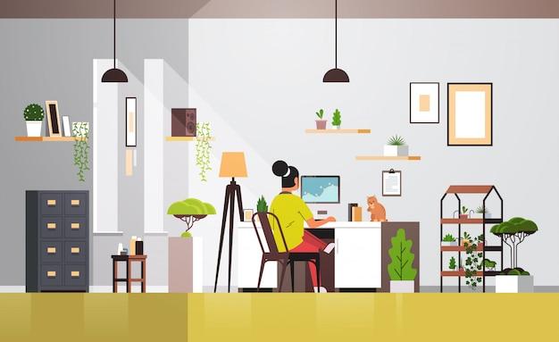 Libero professionista donna utilizzando il monitor del computer che lavora a casa durante la quarantena coronavirus indipendente